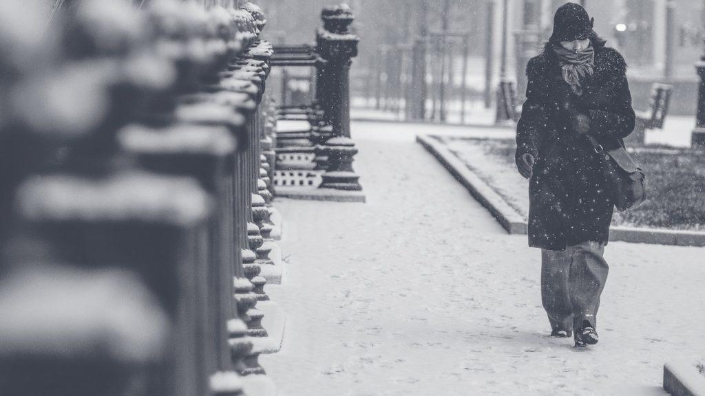 Žena šeta dok sneg pada